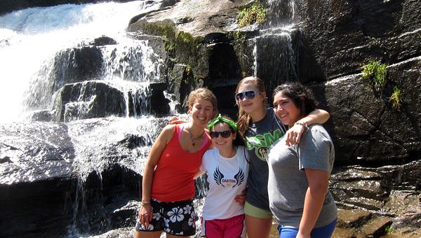 Camp girls hike near waterfall