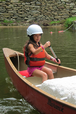 Young camper girl learning to canoe