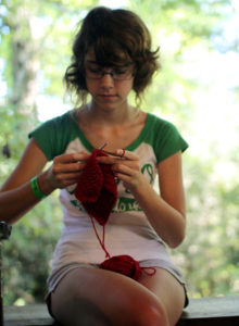 Learning to knit at summer camp