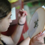 Camp girl doing needlepoint