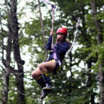 Teen girl riding camp zip line