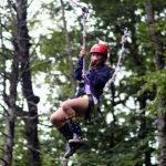 Teen girl riding camp zip line