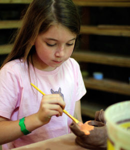 Child glazing a pottery teapot