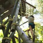 Girl climbing high ropes course at summer camp
