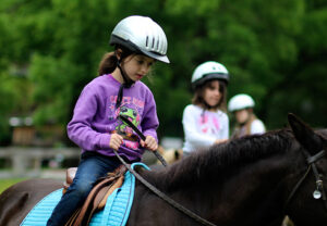 Camp child riding a horse
