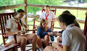 Campers making bracelets on the porch