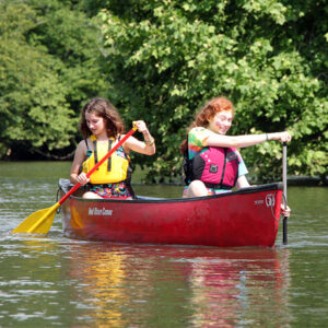 Camp Girls canoeing down a river