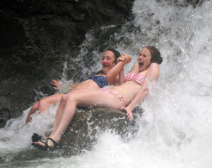 Teens sitting in waterfall