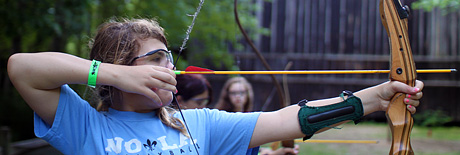 Girl aiming bow and arrow at archery camp activity