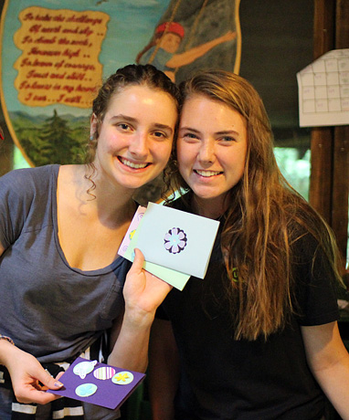 Girls holding cards made at camp