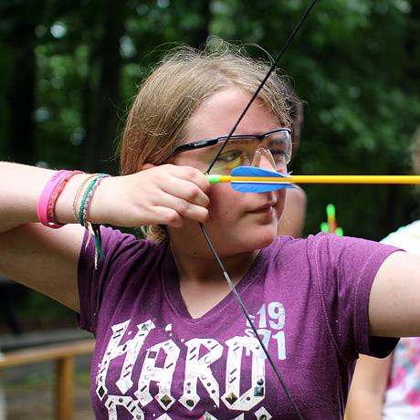 Girl archer aiming her arrow