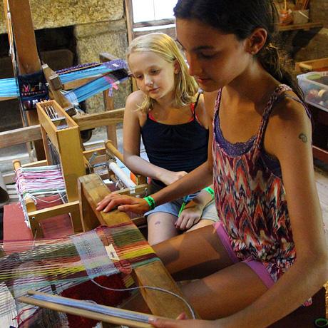 Camp girls weaving on floor loom