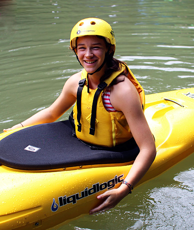 Camp girl smiling in yellow kayak with yellow helmet and pfd