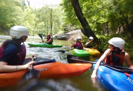 Kids at summer camp kayaking a river