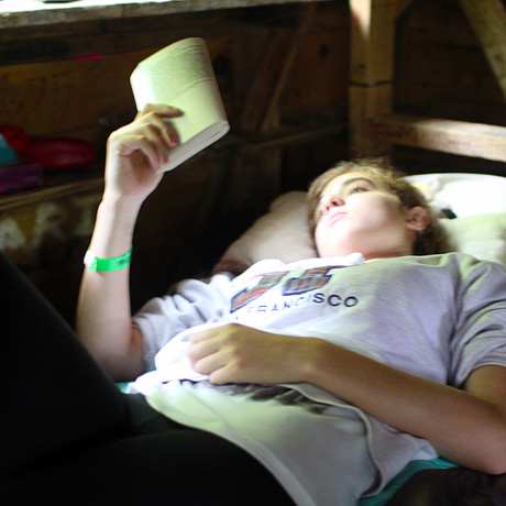 Girl reading book during rest hour at summer camp