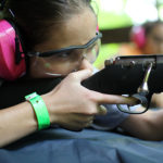 Girl aiming a rifle at summer camp