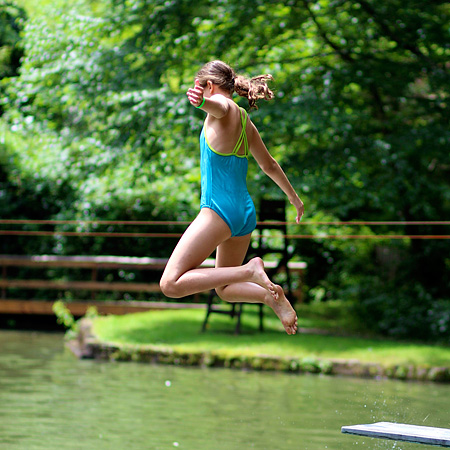 Camp girl jumping in the lake