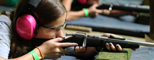 Child aiming a rifle
