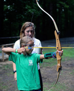 Camp girls having archery instruction