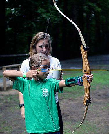 Camp girls having archery instruction