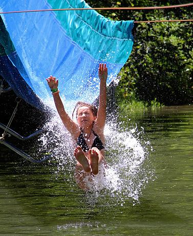Girls splashing into lake from water slide