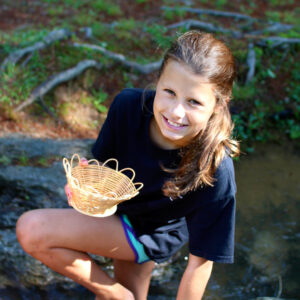 Kid By the creek making a basket