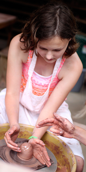 Girl learning to throw pottery on wheel