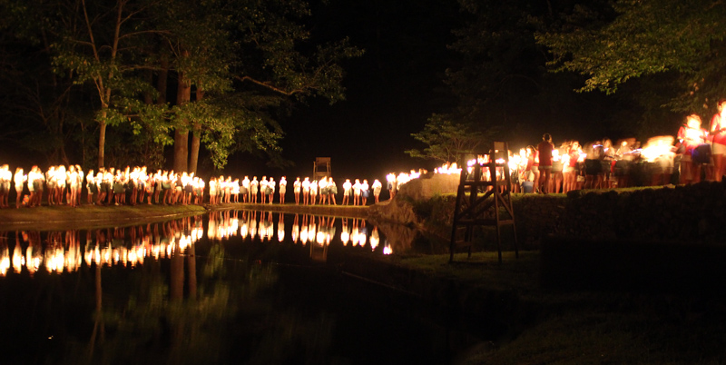 Campers with lit candles around lake