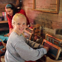 Camper learns to weave at summer camp