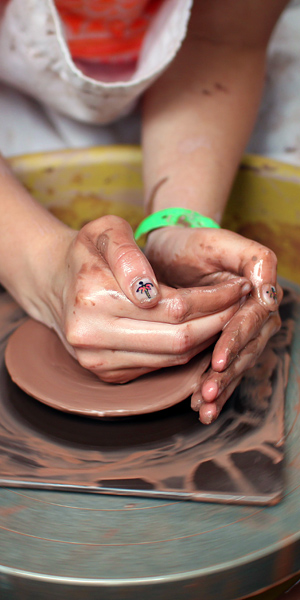 Girls hands on pottery wheel