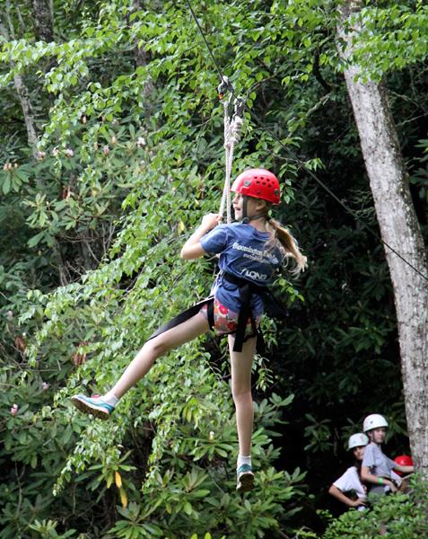 Kid flying on camp zipline