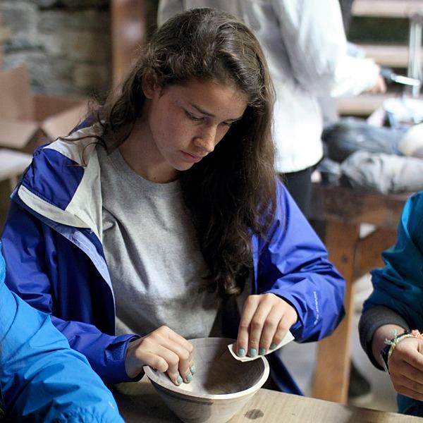 Camper sanding wooden bowl