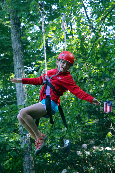 Camp holding USA flag on zipline