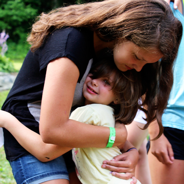 Camper hugs girl to say goodbye from camp