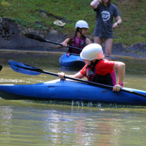 Girls learning to roll a kayak at the lake