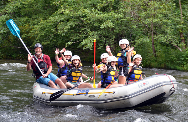 Girls waving while in whitewater rafting boat