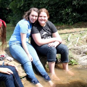 Girls with the feet in a stream