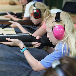Blond girl shooting rifle at summer camp