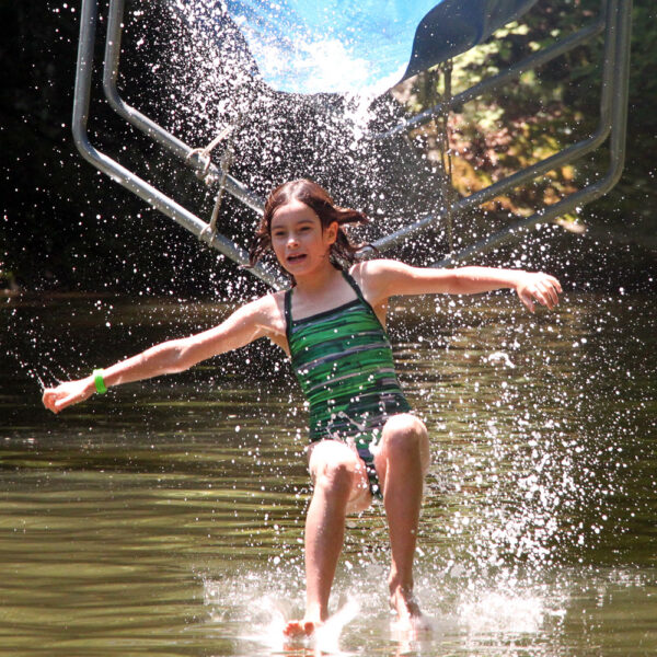 Girl splashes down off camp waterslide