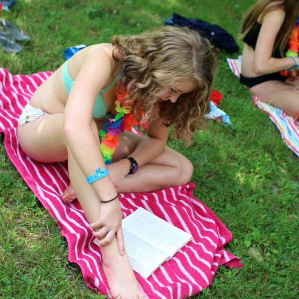 Camp beach girl reading on towel