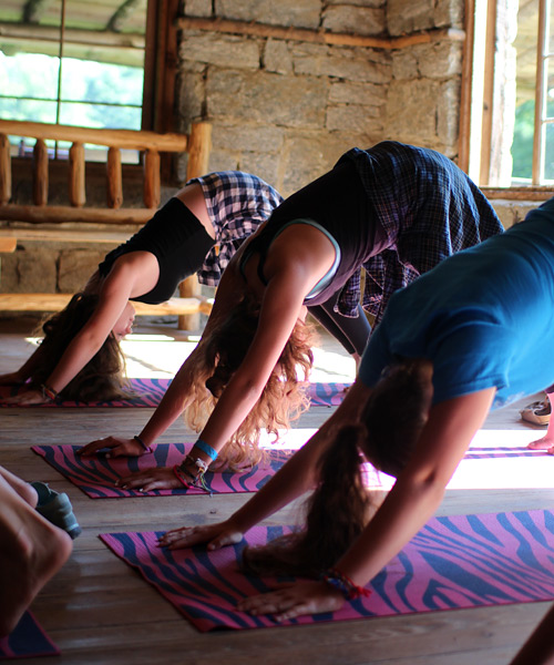 girls in yoga poses at summer camp