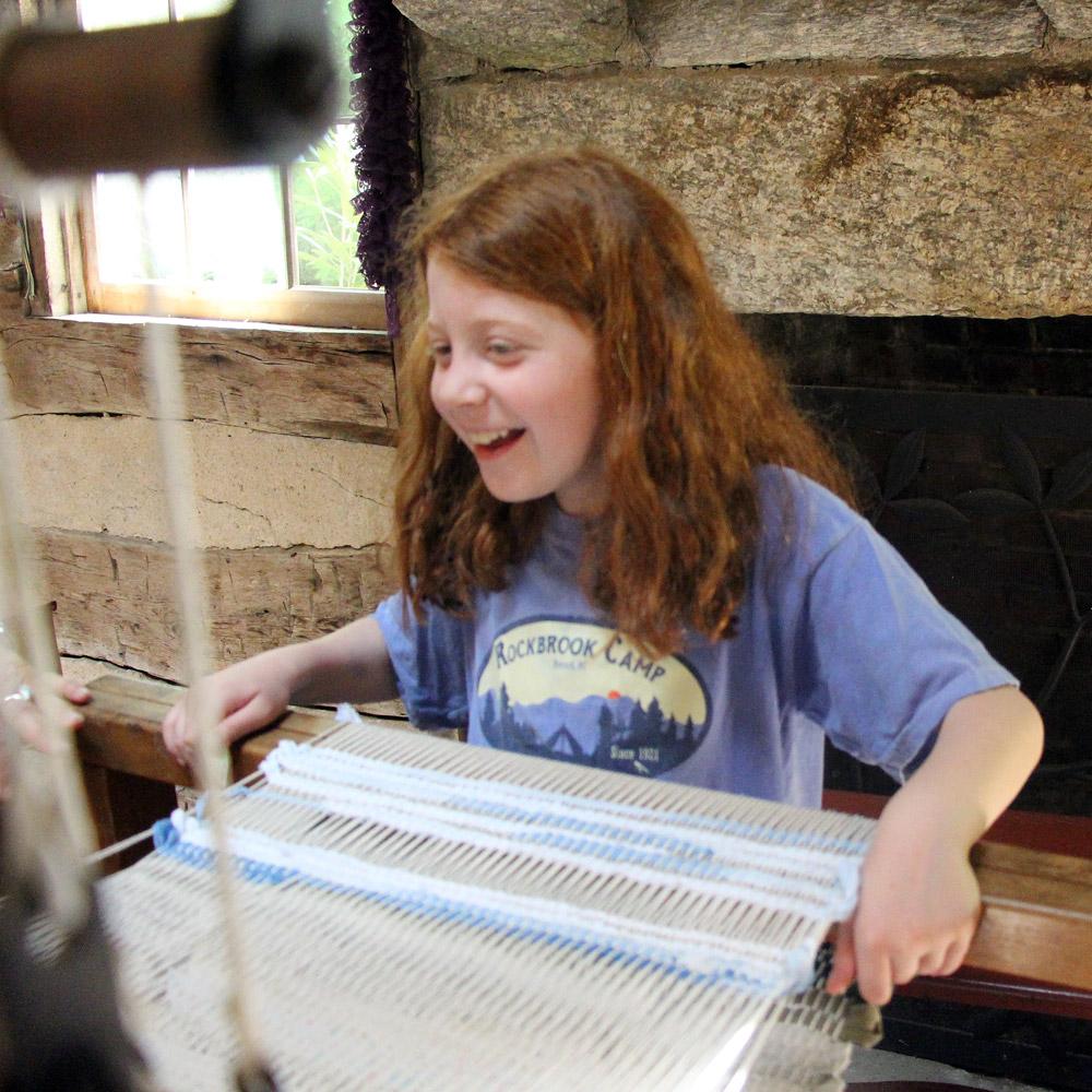 girl weaving on loom