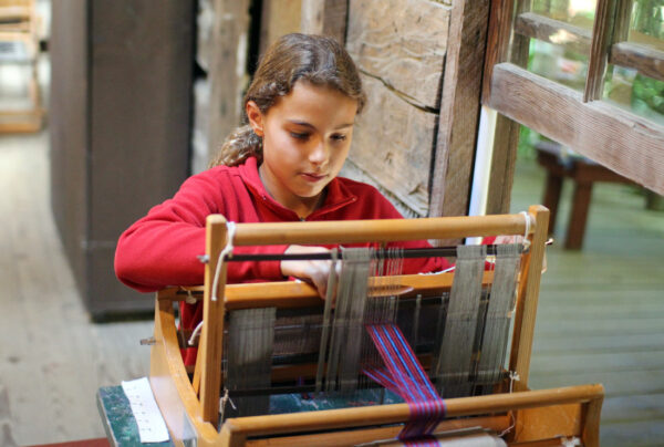 Girl weaving on the tabletop loom