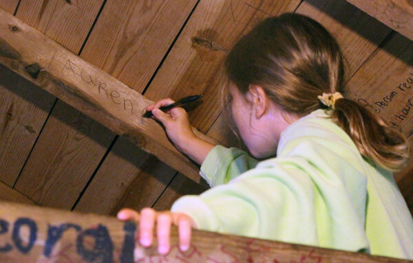 Girl writing her name inside camp cabin