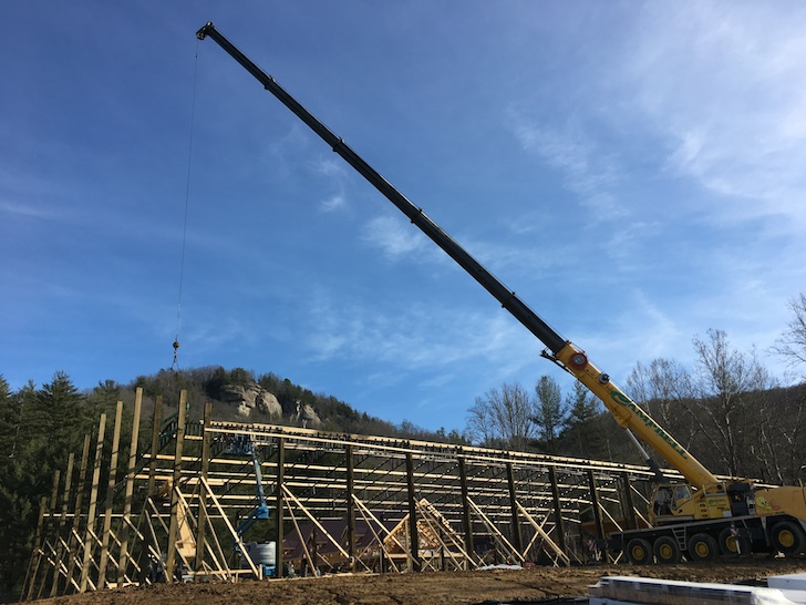Crane lifting steel trusses for horse arena