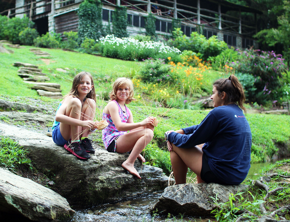 Two girls and counselor weaving baskets by the creek