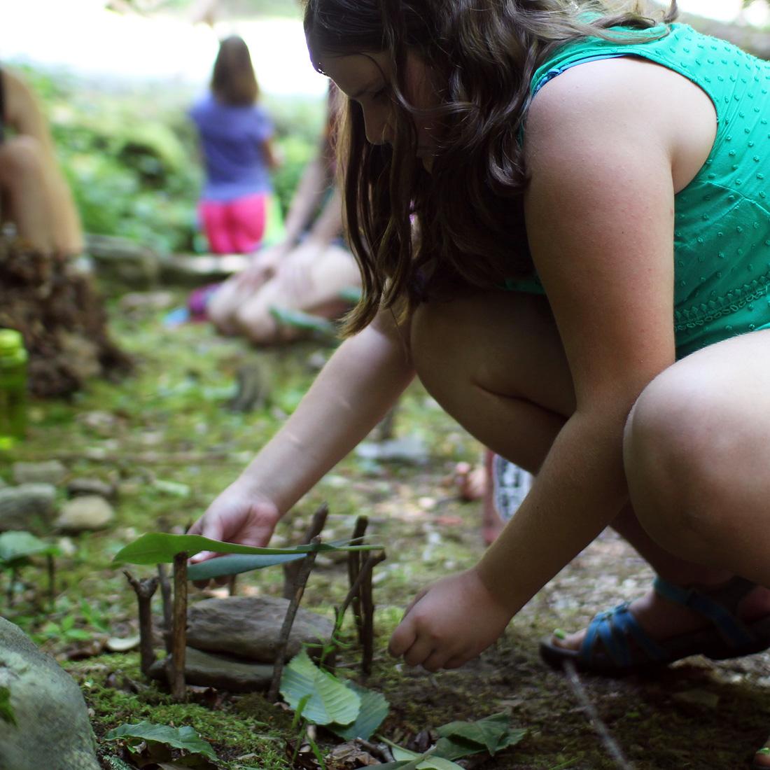 girl building fairy house