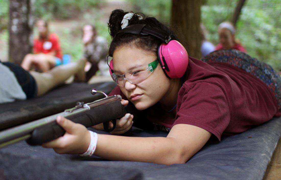 camp girl aiming rifle