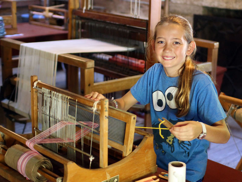 Camp girl using table loom for weaving