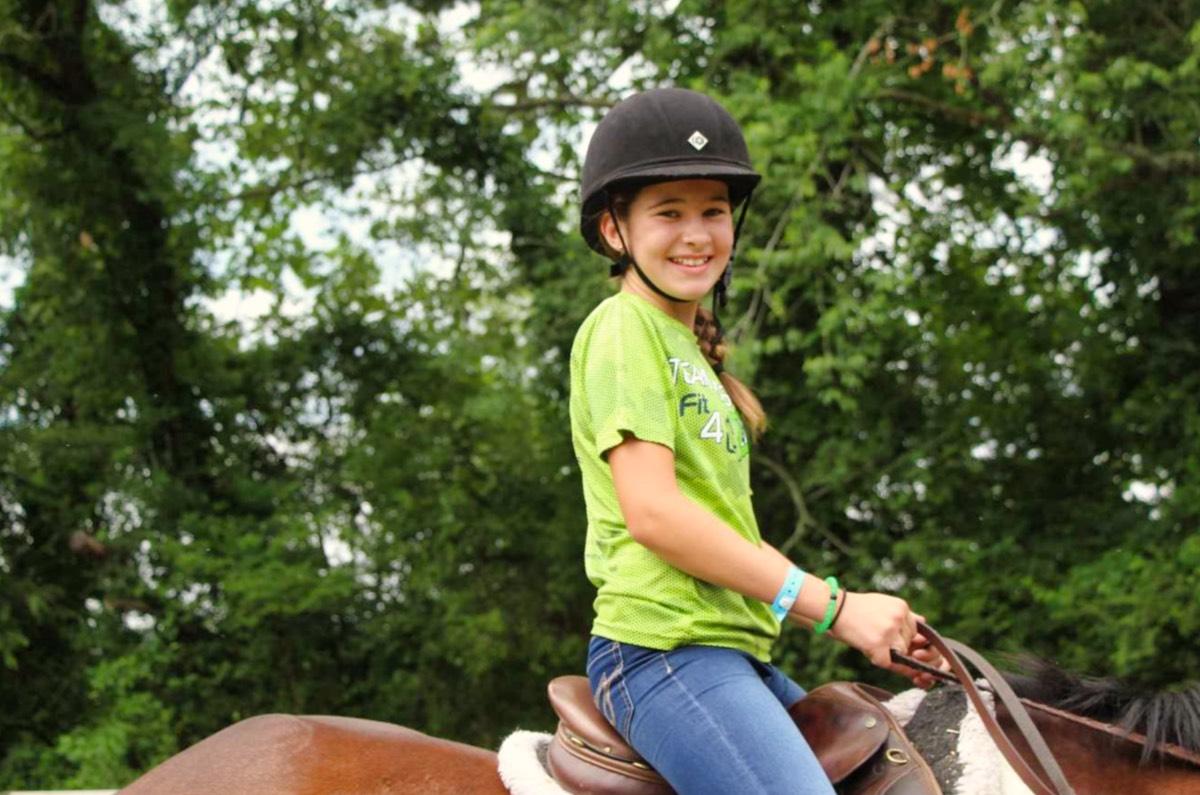 camp girl riding a horse